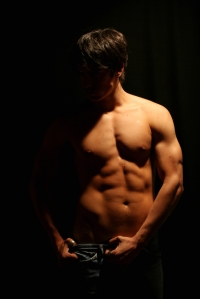 Attractive man body muscles in dark shadow. Dramatic Contrast light